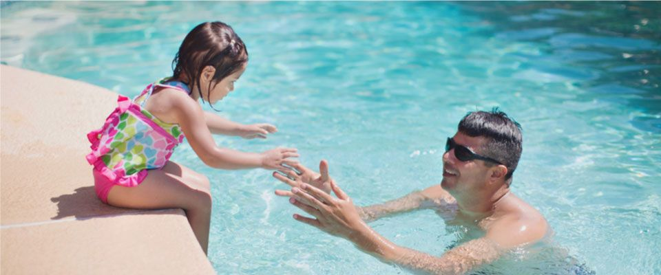 Father and baby daughter in pool